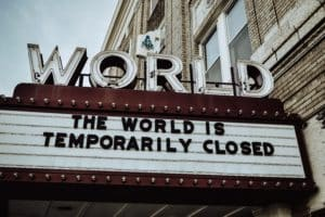 Sign on building stating The Word Is Temporarily Closed - Is Real Estate Still a Good Investment During Covid?