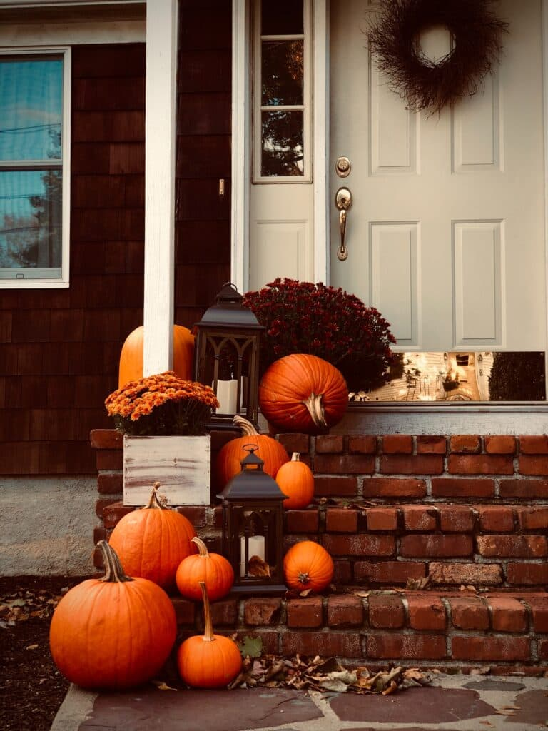 Front door of house with outdoor fall decor of autumn wreath, brick steps leading to front door decorated with pumpkins, mums, and outdoor lanterns