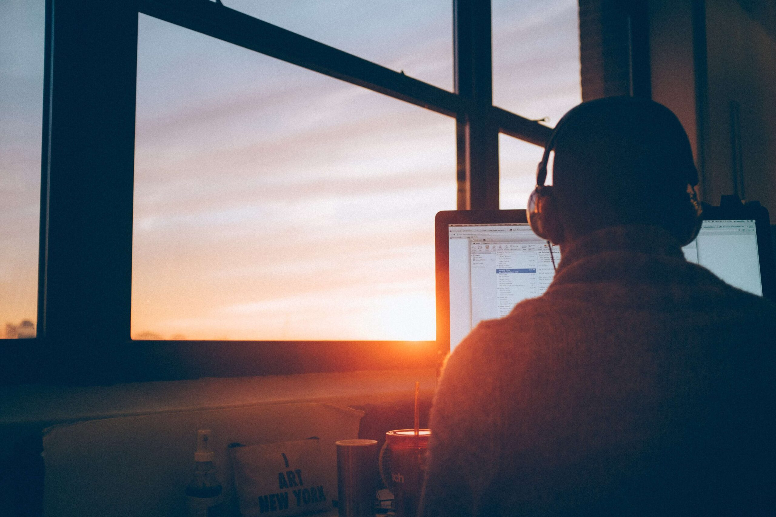 man with back to computer screen facing window with sunset conducting masterclass on How to invest in real estate the safe and easy way even if you don't have a lot of money