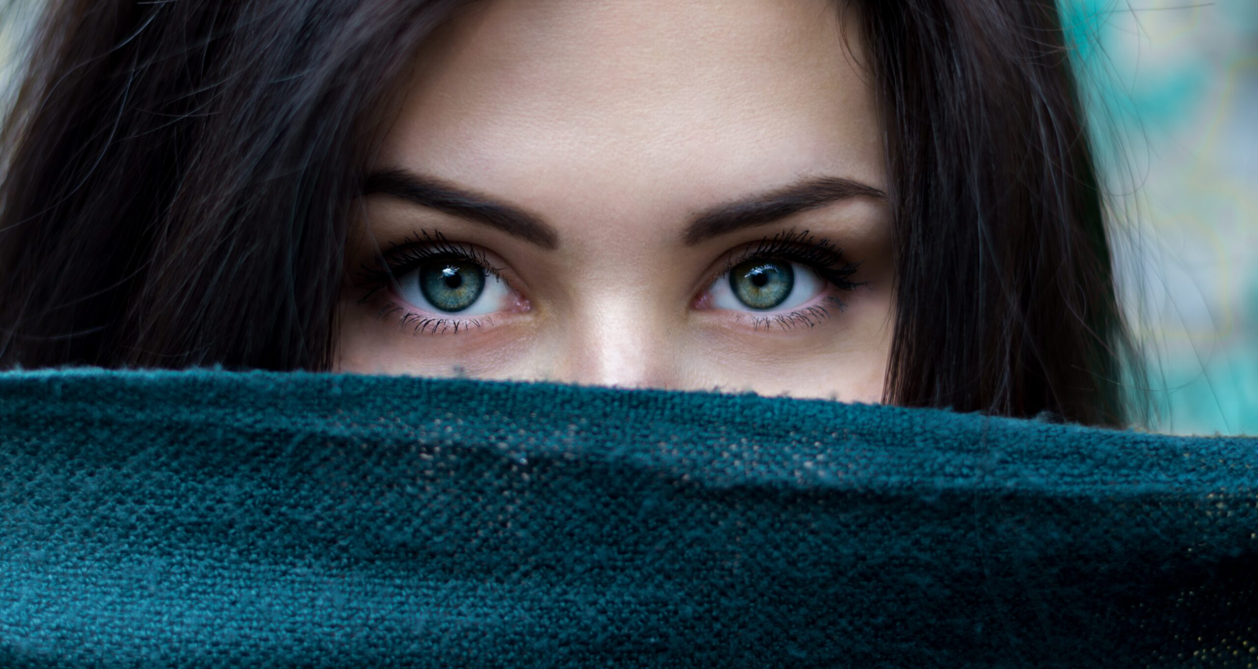 Woman with blue eye and brown hair looking over blue scarf - How To Use Your Body To Deliver Your Real Estate Presentation