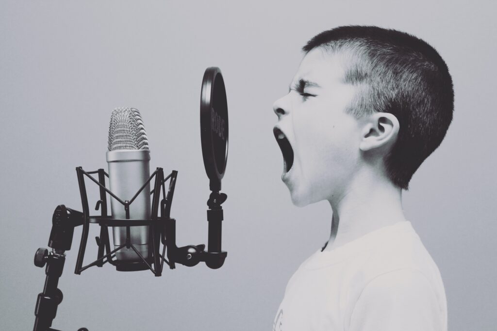 young boy yelling into a microphone - How To Use Your Body To Deliver Your Real Estate Presentation