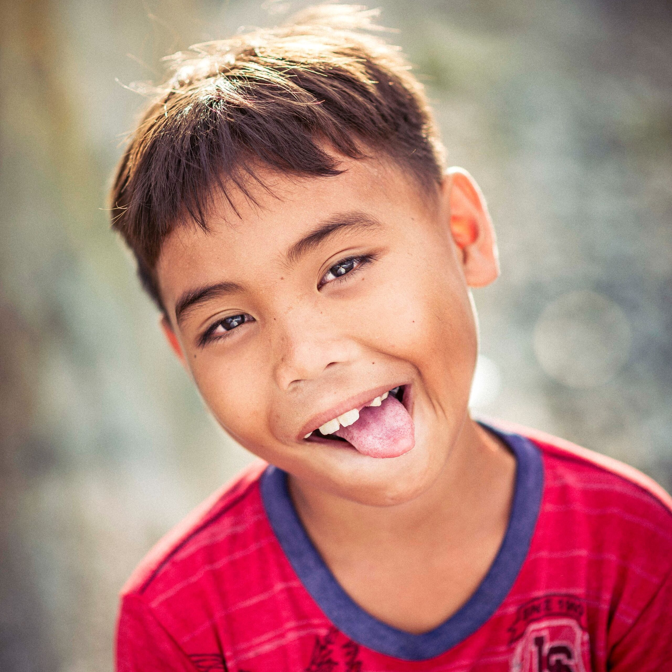 young boy with tshirt smiliing and sticking tongue out - how you use your body to deliver your real estate presentation