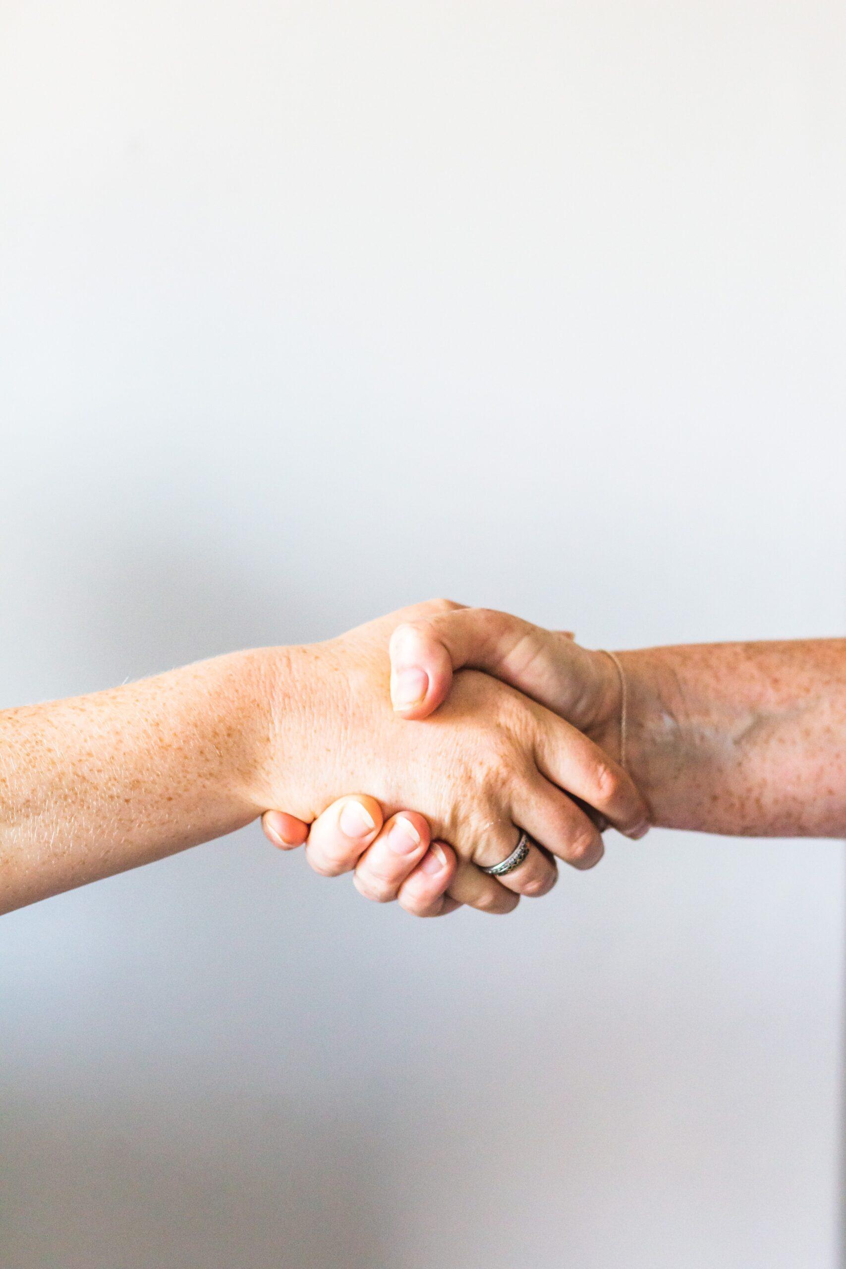 hand shake between 2 people - decluttering your home