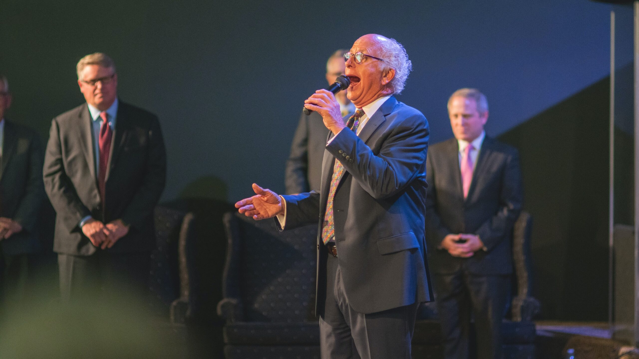 old man standing with microphone delivering a speech with men standing to the right side - how you use your body to deliver your real estate presentation