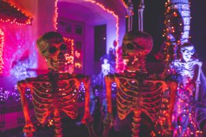 two prominant skeletons in red lights facing each other, 3 other white lit skeletons in background for halloween scene in front of house - tenant screening