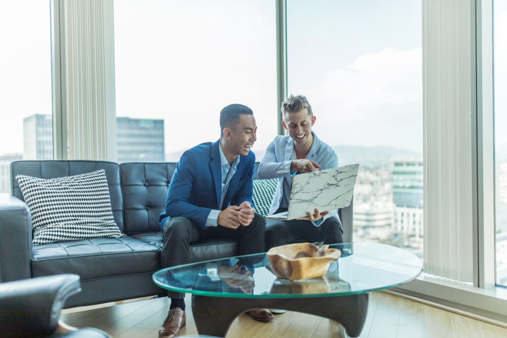 two men viewing images on a lap top in a penthouse apartment