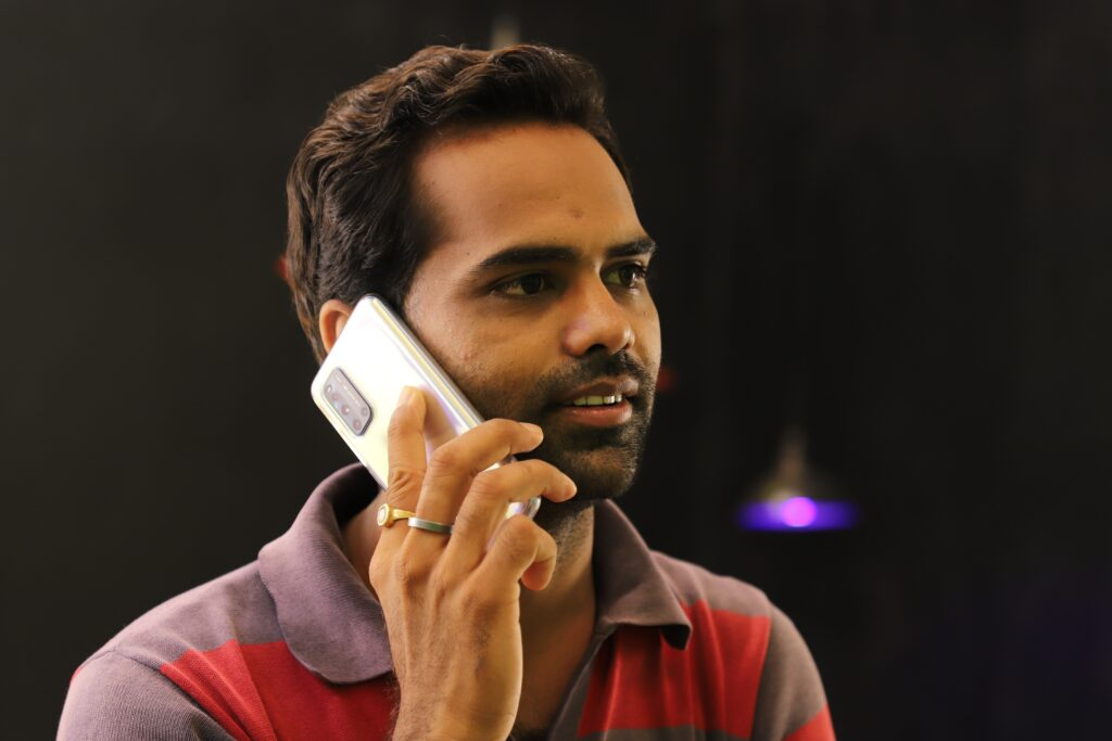 East Indian man in striped shirt talking on a cell phone