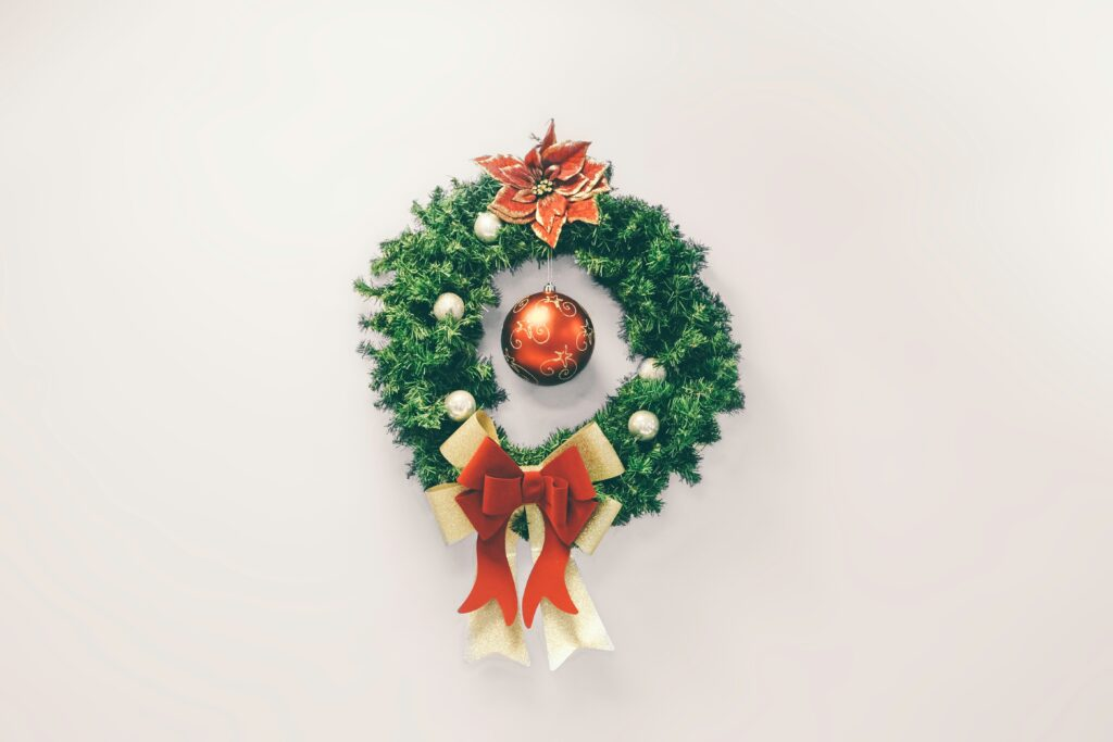 simple green wreath, with white ornaments, red poinsetta, red ornament in centre and red/gold bows on bottom - Christmas Décor Inspiration