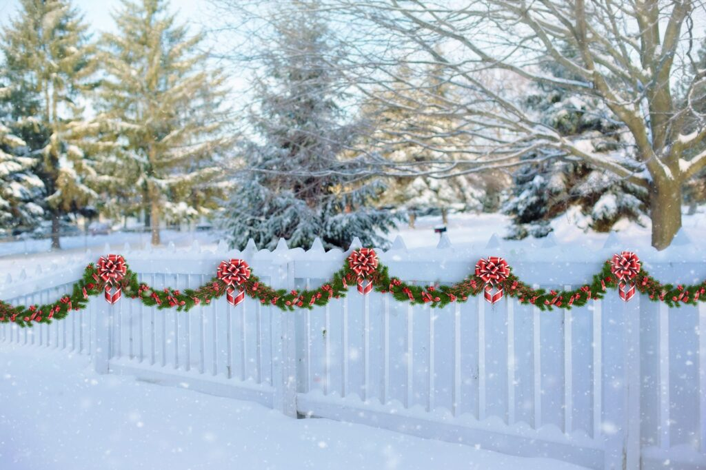 Outdoor green red gardland on white fence -Christmas Décor Inspiration