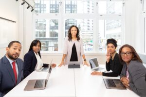 young smiling woman standing at the front of a board room meeting with 4 business participants - 7 Tips for Delivering Your Killer 45-Minute Presentation