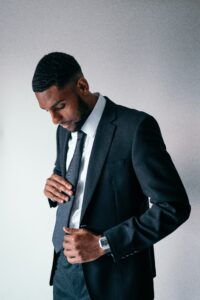 young handsome black man adjusting gray tie, wearing a gray suit - Presentation apparel, what to wear for your presentation