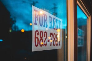 For rent sign in red letteriing with phoen number in window