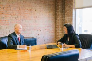 meeting between man and woman in board room - 21 CRITICAL QUESTIONS TO ASK BEFORE HIRING A PROPERTY MANAGER