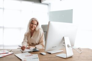 60ish woman sitting in front of desktop with pleasant expression - Top 3 Tips for Screening Your Tenant References