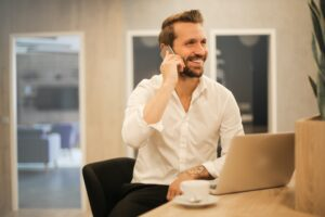 Man sitting at desk smiling, talking on telephone - How to Pre-Screen your Tenants in 5 Easy Steps