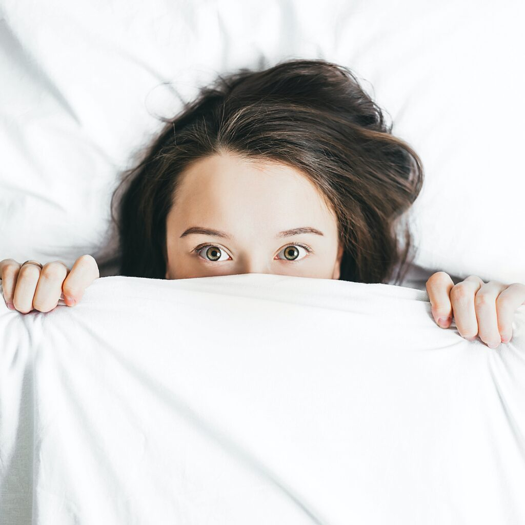 young woman with long brown hair in bed looking scared wtih covers pulled up under her nose - I can't do public speaking it makes me nervous
