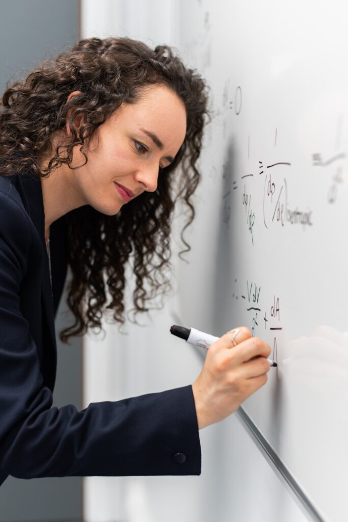 woman with long curly brown hair writing formula on white board - formula for public speaking