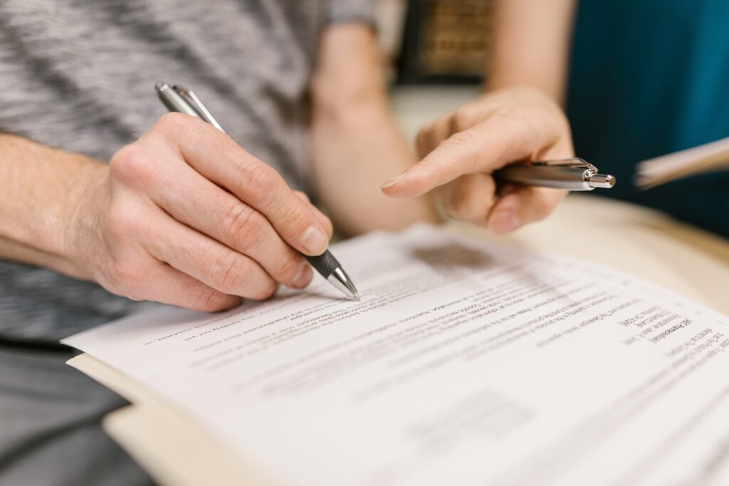 person in gray tshirt signing lease- Fixed term or periodic term tenancy/