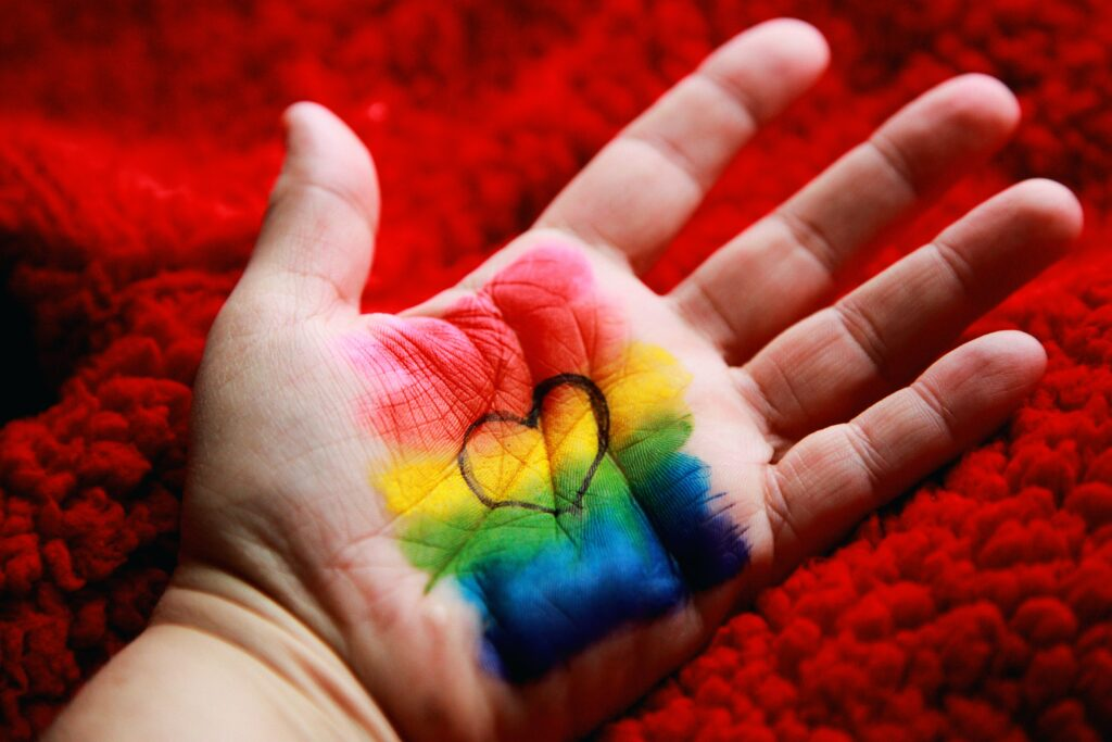 Male hand with rainbow colours and heart drawn on palm- The Human Rights Act and your Rental Property Business