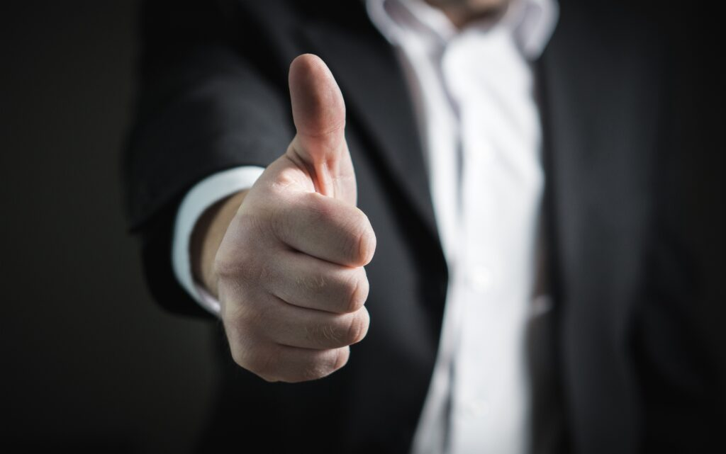 man in black suit and white shirt holding a thu,bs up position - Are you setting your rental property up for success? What type of landlord are you?
