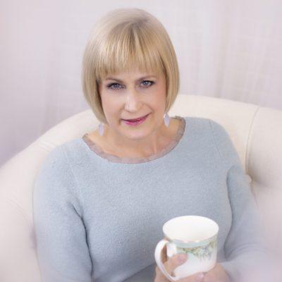 Nelda Schulte holding a mug - why I do what I do using real estate as the tool